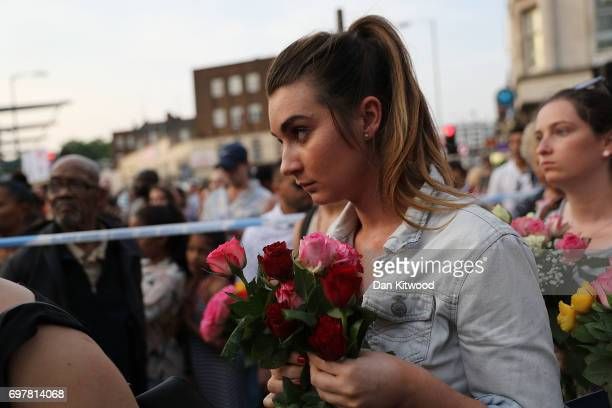 A women hold flowers as she attends a vigil outside Finsbury Park Mosque on June 19 2017 in London England Worshippers were struck by a hired van as...