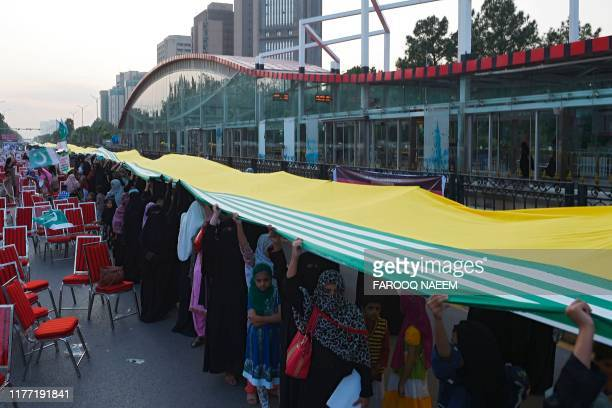 Women hold giant Pakistanadministered Kashmir flag at the Kashmir Million March and World Largest Flag demonstration in Islamabad on October 20 to...