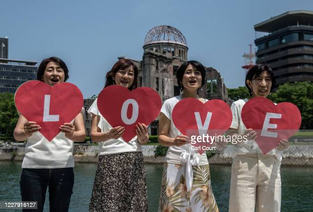 Women hold heartshaped cards reading love as they sing into a camera near the Atomic Bomb Dome on August 5 2020 in Hiroshima Japan This Thursday will...
