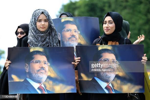 Women hold images of former Egyptian President Mohamed Morsi at the funeral prayer in absentia for him at Konak Square in Izmir, Turkey on June 18,...