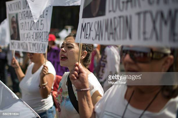 Women hold photographs of their disappeared son during a march on Mother's Day on May 08 2016 in Mexico City Mexico Mothers and other relatives of...