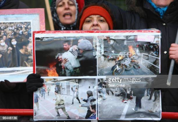 Women hold photographs showing scenes from recent violent, anti-government demonstrations in Tehran while protesting outside the Iranian embassy on...