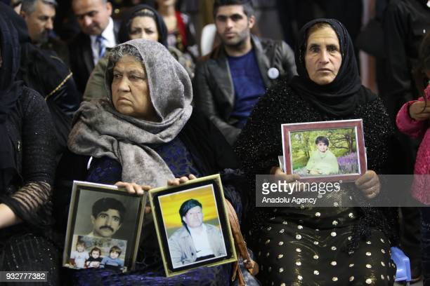 Women hold pictures of their relatives as people visit the Halabja Martyrs Monument to commemorate the victims of Halabja massacre due to 30th...
