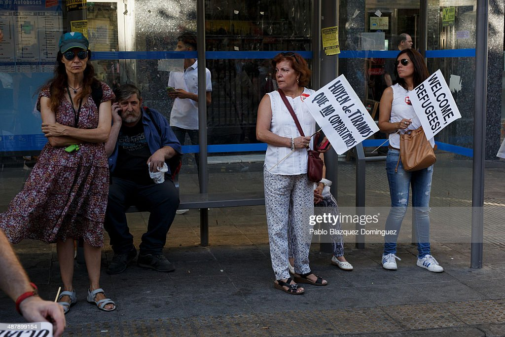 Women hold placards at a bus stop reading 'They are fleeing from tyrants that we don't fight' (L) and 'Welcome refugees' (R) during a demonstration to show solidarity and support for refugees on September 12, 2015 in Madrid, Spain. Several cities across Spain have called for demonstrations under the slogan 'Welcome refugees. For a more responsible European policy'. Europe is facing the region's largest crisis of migrants and refugees since World War II. Spain would have to take nearly 15,000 refugees under a new European Union plan to relocate 120,000 refugees. Many Spanish cities and citizens took the lead on offering their support to refugees.