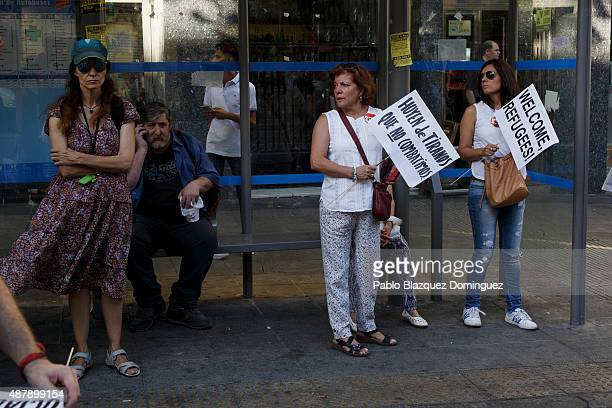 Women hold placards at a bus stop reading 'They are fleeing from tyrants that we don't fight' and 'Welcome refugees' during a demonstration to show...