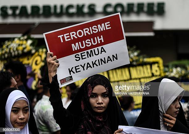 TOPSHOT Women hold placards during a vigil outside the damaged Starbucks coffee shop in central Jakarta on January 15 a day after a series of...