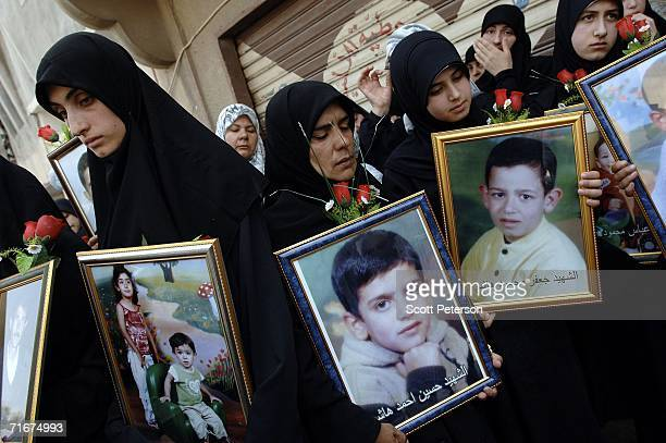 Women hold portraits of dead children as most of the civilian victims of an Israeli air strike are formally buried August 18 2006 in Qana Southern...