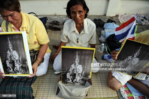 Women hold portraits of Thai King Bhumibol Adulyadej as they sit on the sidewalk outside the Royal Palace on the eve of his Coronation Day...
