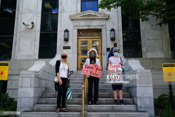 Women hold signs as they watch the body of civil rights leader C.T. Vivian carried off the grounds of the Georgia Capitol building on July 22, 2020...