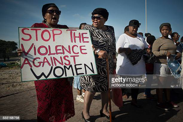 Women hold signs during a protest against ongoing violence against women in Gugulethu on May 21 about 20 Km from the centre of Cape Town This protest...