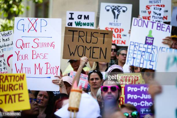 Women hold signs during a protest against recently passed abortion ban bills at the Georgia State Capitol building, on May 21, 2019 in Atlanta,...
