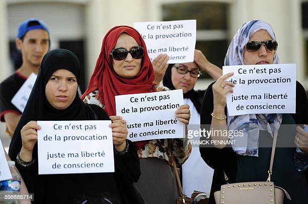 "Women hold signs reading ""Is it not a provocation, just my freedom of conscience"" during a ""headscarf march"" organized by the Collective against..."