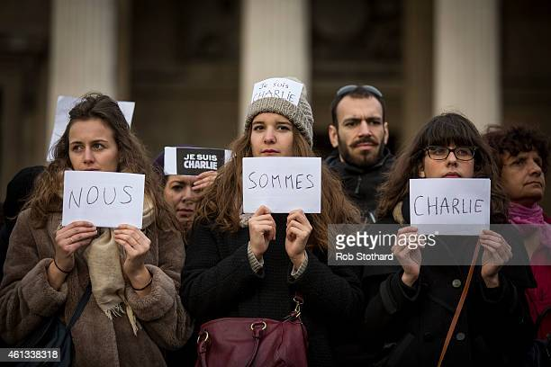 Women hold signs reading 'Nous sommes Charlie' as people gather in Trafalgar Square to show their respect to victims of the terrorist attacks in...