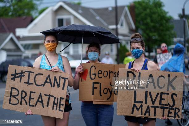 TOPSHOT Women hold signs while protesting near the area where a Minneapolis Police Department officer allegedly killed George Floyd on May 26 2020 in...