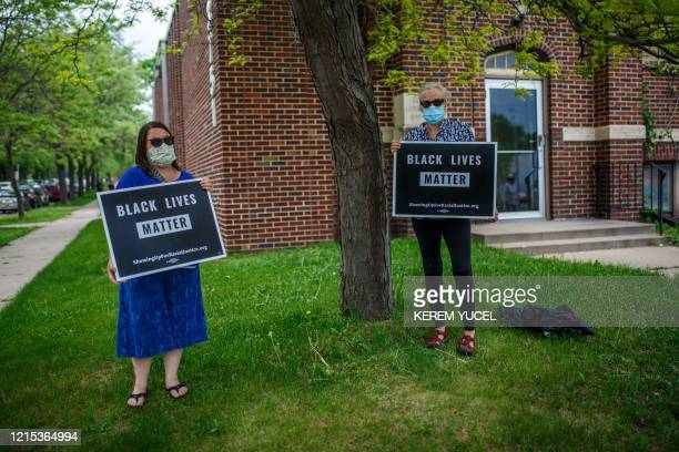 Women hold signs while protesting near the area where a Minneapolis Police Department officer allegedly killed George Floyd on May 26 2020 in...