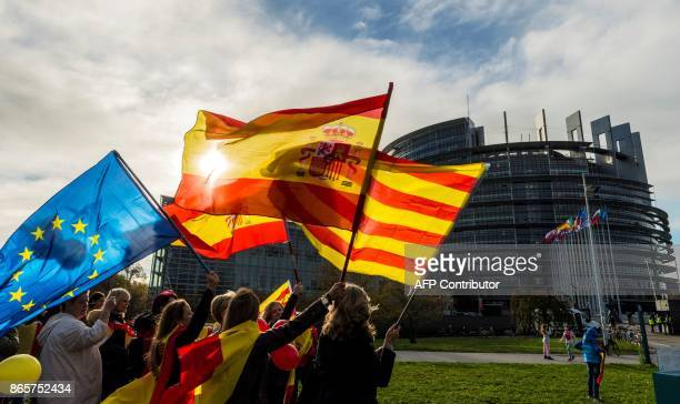 Women hold Spanish, Catalan and European flags during a demonstration against Catalonia's independence in front of the European Parliament building...