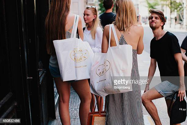 Women hold Steve Madden Ltd shopping bags while standing outside of a shop in the SoHo neighborhood of New York US on Wednesday June 18 2014 The...