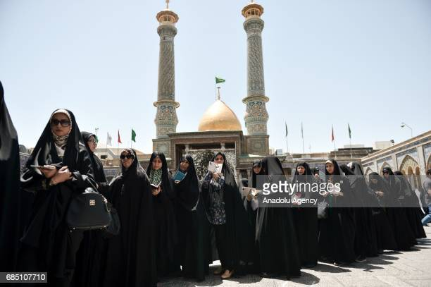 Women hold their identity cards as they wait to cast their ballots during Iran's 12th presidential election at Shah Abdol Azim mosque in Tehran Iran...