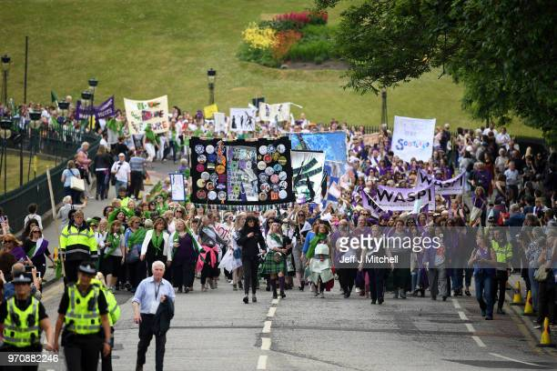 Women hold up banners as they march during Processions 2018 to mark 100 years since women won the right to vote in the UK on June 10 2018 in...
