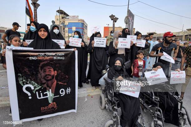 Women hold up protest signs demanding authorities to hold accountable the killers of dozens of activists during a demonstration at Haboubi Square in...