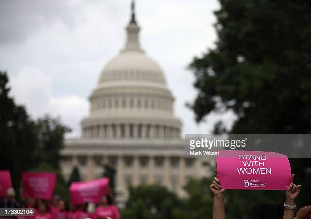 Women hold up signs during a women's pro-choice rally on Capitol Hill, July 11, 2013 in Washington, DC. The rally was hosted by Planned Parenthood...