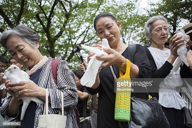 Women hold white doves before releasing them as a tribute to the war dead at the Yasukuni Shrine on the anniversary of Japan's World War II surrender...