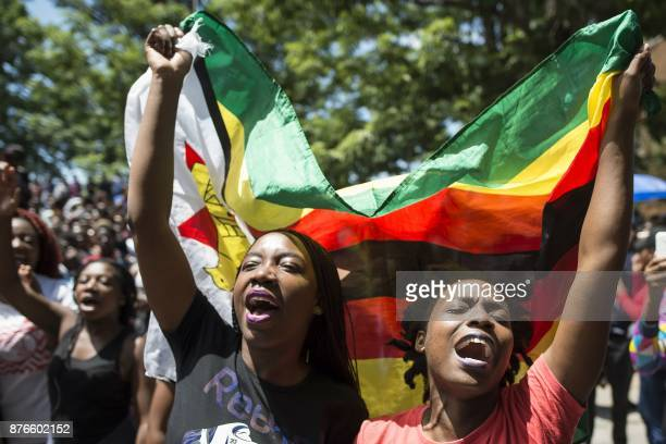 Women holding a flag of Zimbabwe take part in a demonstration of University of Zimbabwe's students on November 20 2017 in Harare to demand the...