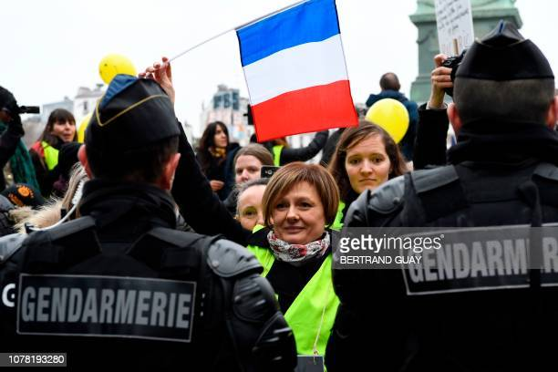 Women holding a French national flag gesture in front of French gendarmes during a rally of the Women's Yellow Vest protest movement in Paris on...