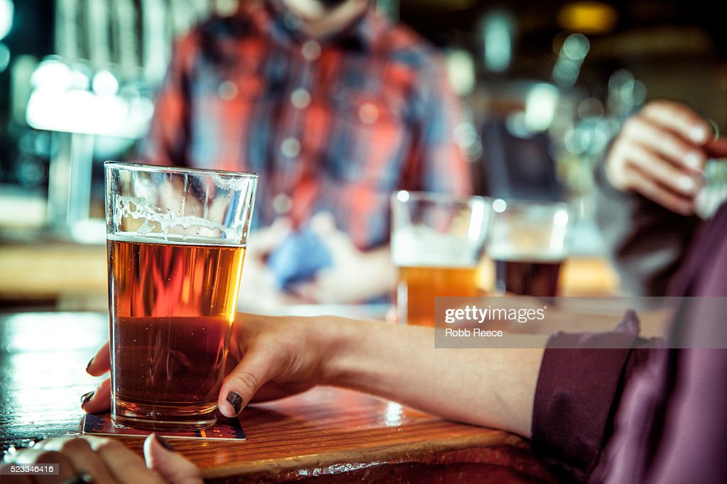 A women holding a glass of beer at a bar : Stock Photo