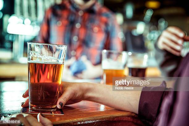 a women holding a glass of beer at a bar - robb reece stock pictures, royalty-free photos & images