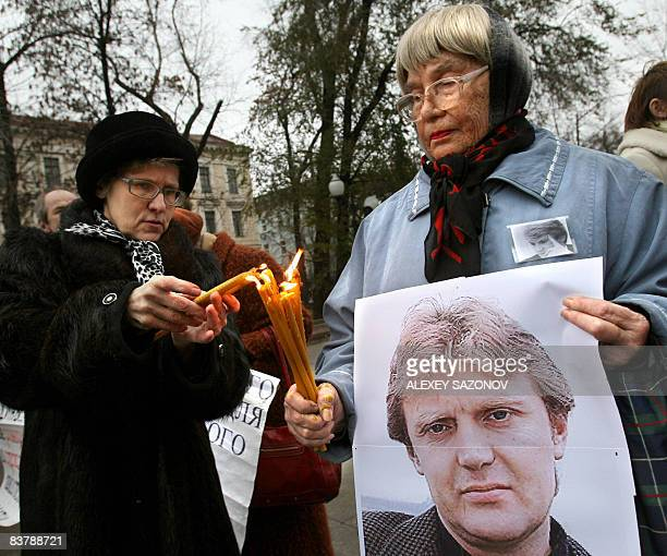 Women holding a poster of deceased former Russian spy Alexander Litvinenko light candles in his honor in Moscow on November 22 2008 The man accused...