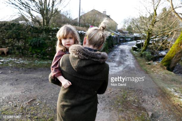 a women holding a young girl as she walks down an empty country lane. - femalefocuscollection stock pictures, royalty-free photos & images