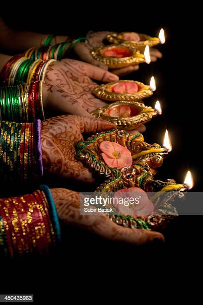 Women holding decorated earthen lamps at Diwali