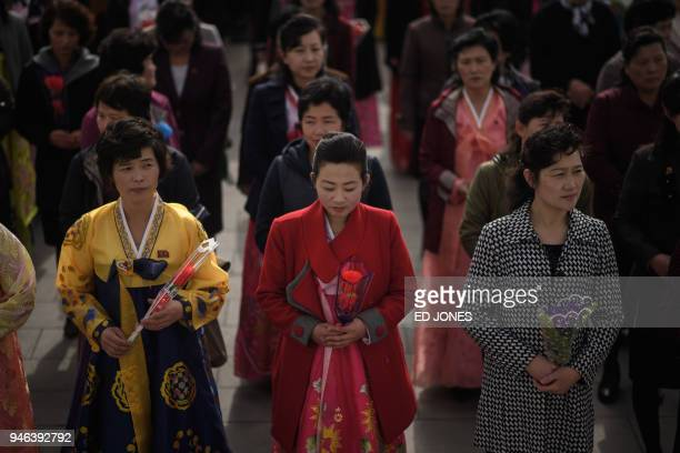 Women holding flowers arrive to pay their respects before the statues of late North Korean leaders Kim Il Sung and Kim Jong Il at Mansu hill in...