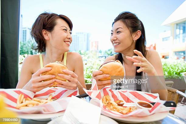 Women holding hamburgers, smiling
