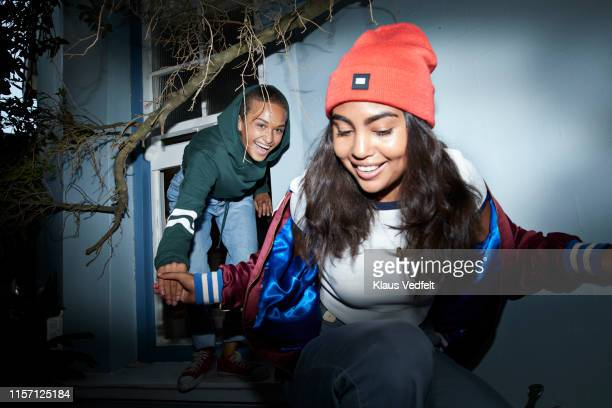 women holding hands and laughing while sneaking out of window - falsenews stock pictures, royalty-free photos & images