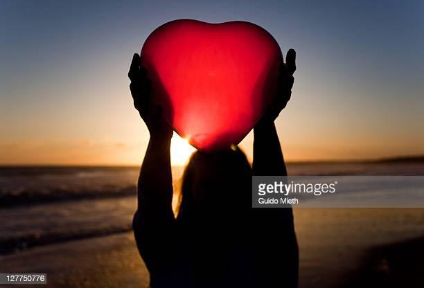 Women holding heart over her head in sunset.