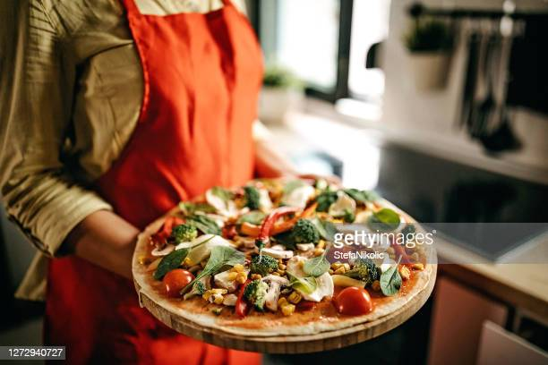 women holding homemade pizza, preparing for cooking - crucifers stock pictures, royalty-free photos & images