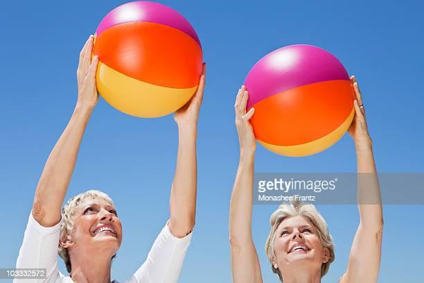 Women holding multicolor beach balls against blue sky