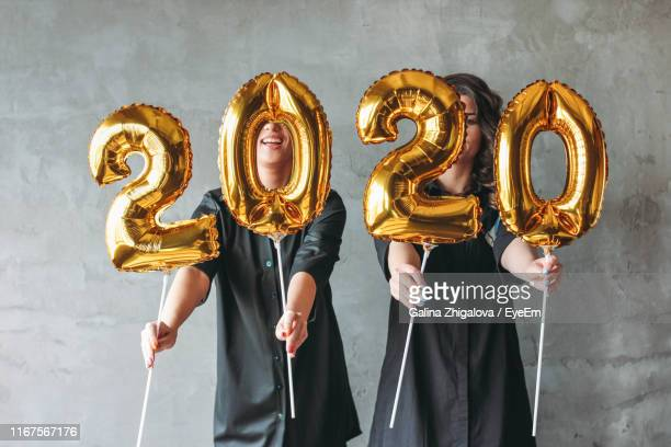 women holding number shaped helium balloons in new year party - 2020年 ストックフォトと画像