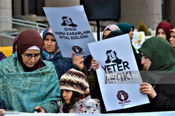 Women holding placards and a girl stand behind a banner as an organized group of proIslamic demonstrators makes a statement outside the main...