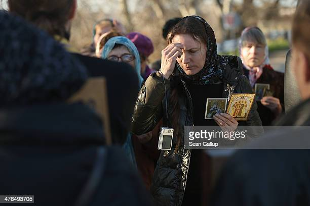 Women holding religious icons and led by Orthodox priests pray for peace before allowing pro-Russian militants to kiss large icons at a checkpoint on...