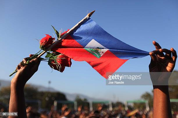 A women holds a Haitian flag and roses as people pray together during a church service that is set up outdoors near an encampment after numerous...