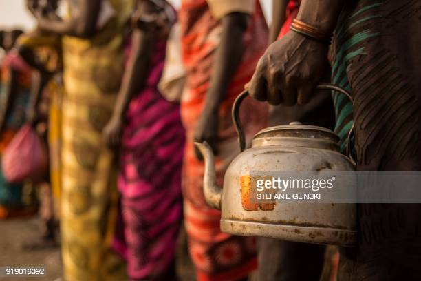 A women holds a kettle to receive salt during a monthly food distribution at the Protection of Civilian site in Bentiu South Sudan on February 15...
