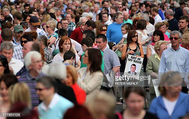 A women holds a placard of murdered Police Constable Ronan Kerr amoung thousands of people as they attend a walk through the County Tyrone town of...