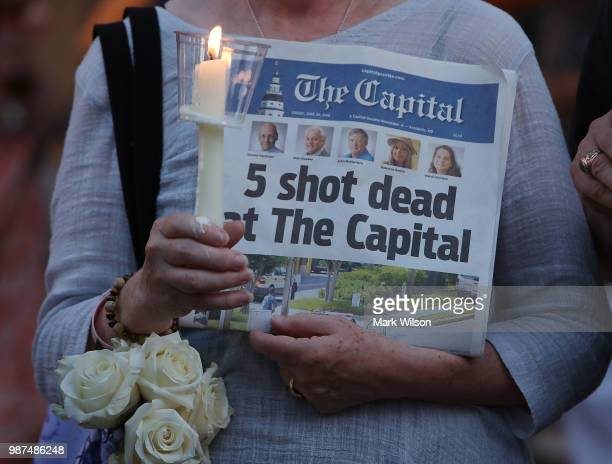 A women holds today's edition of the Capital Gazette newpaper during a candlelight vigil to honor the 5 people who were shot and killed yesterday on...
