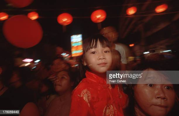 A women holds up a child for a better view during the Chinese new year festivities in the Yaowarat area of Bangkok The chinese community constitutes...