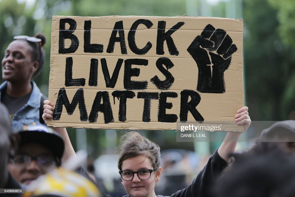 A women holds up a placard with the slogan 'Black Lives Matter' as people gather in Brixton, south London to protest against police brutality in the US, on July 9, 2016, after two recent incidents where black men have been shot and killed by police officers. / AFP / Daniel Leal-Olivas