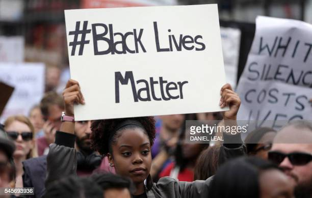 A women holds up a placard with the slogan 'Black Lives Matter' as people gather in Brixton south London to protest against police brutality in the...