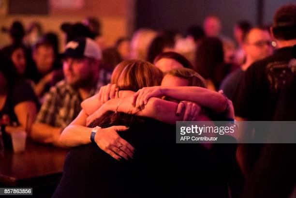 Women hug at a fundraiser for victims of the Las Vegas massacre and their families October 4 2017 at Stoney's Rockin' Country bar and country music...